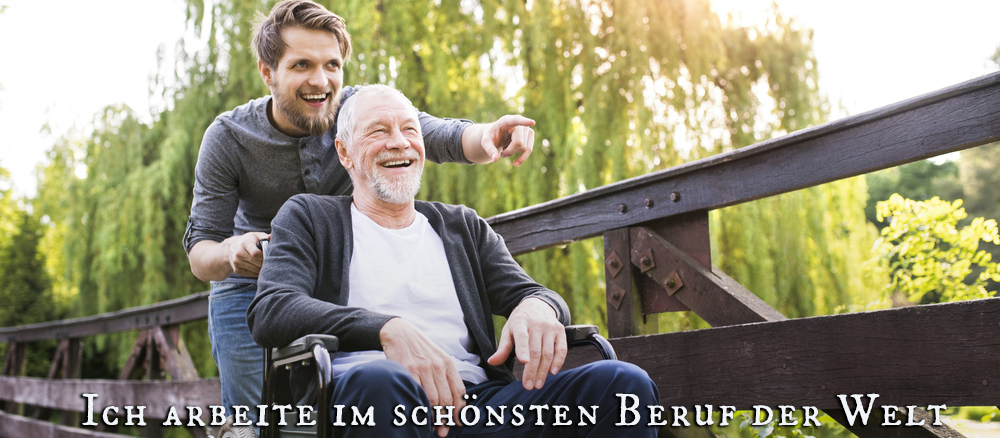 Pfleger fährt Patienten im Rollstuhl